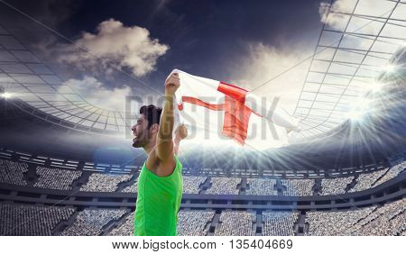 Profile view of sportsman holding an England flag against rugby stadium