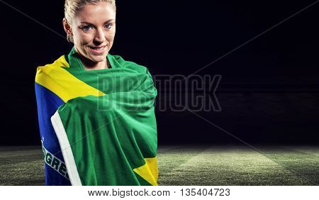 Athlete with brazilian flag wrapped around her body against rugby stadium