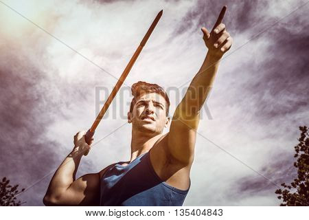 Low angle view of sportsman practising javelin throw against view of balloons in the sky