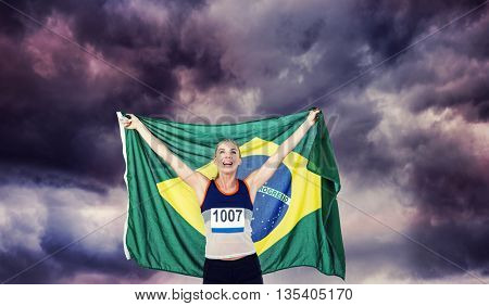 Athlete posing with brazilian flag after victory against gloomy sky