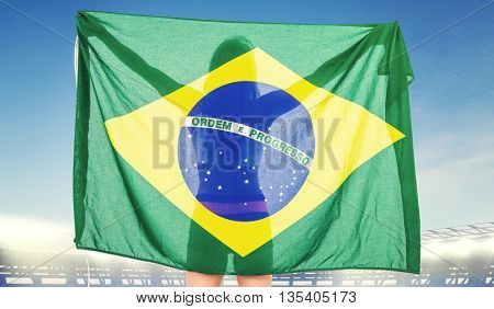 Athlete posing with brazilian flag after victory against large football stadium under bright blue sky