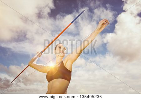 Low angle view of sportswoman is practising javelin throw against blue sky with white clouds