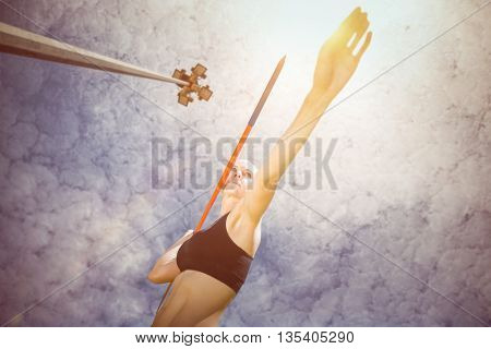 Sporty woman preparing her javelin throw against low angle view of floodlight