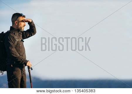 Side view of bearded climber protecting eyes from the sun while looking away.Copy space