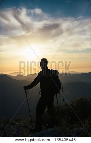 Back view of unrecognizable backpacker watching sunset in mountains.Copy space. Backlighting