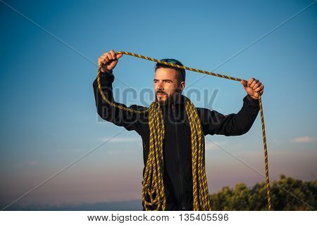 Portrait of bearded adult man with yellow rope looking away.Blue sky on background