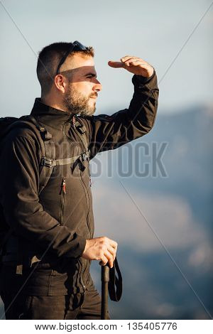 Side view of adult bearded man protecting his eyes from the sun while looking away