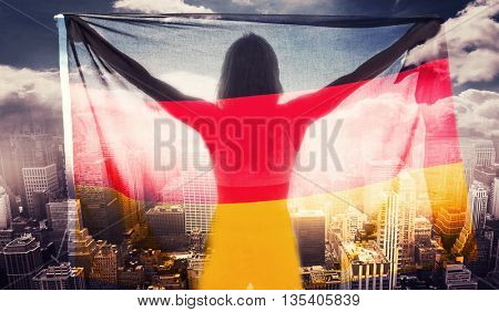 Athlete posing with german flag after victory against aerial view of a city on a cloudy day