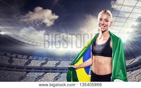 Athlete with brazilian flag wrapped around his body against rugby stadium
