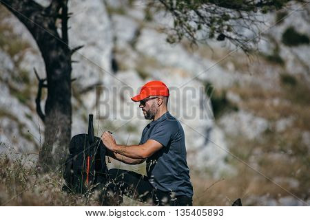 Side view of bearded man in cap and sunglasses preparing his backpack in sunlight on grass