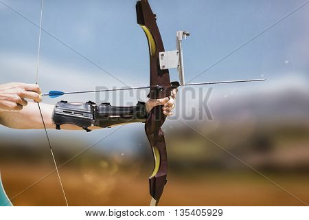 Close up of someone practising archery against country scene with mountain
