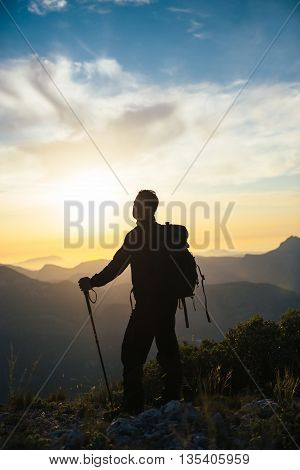 Back view of unrecognizable adult man with backpack and stick looking away in evening mountains