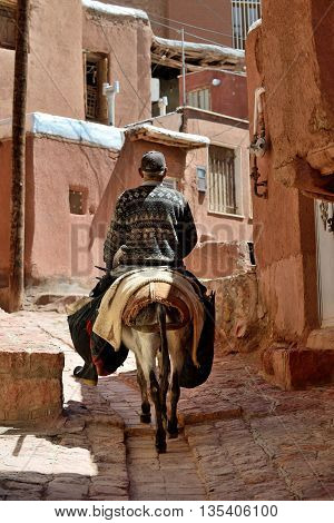 ABYANEH - APRIL 20: Unknown old man riding in street of Abyaneh, Iran on April 20, 2015. Abyaneh is small mountain village, at the 2006 census, its population was 305, in 160 families.