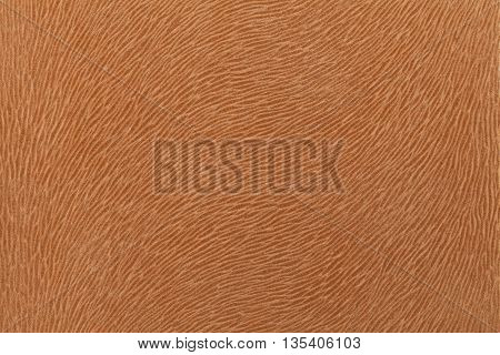Matte brown fabric imitating animal fur. Leather background. Textured cloth.