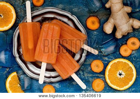 Homemade orange and carrot natural juice popsicles with turmeric honey and ginger