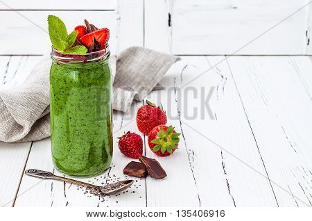 Healthy breakfast green smoothie with superfoods. Matcha green tea chia seeds pudding dessert with fresh mint strawberries and chocolate on white rustic table