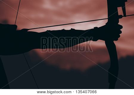 Close up of man stretching his bow against trees and mountain range against cloudy sky