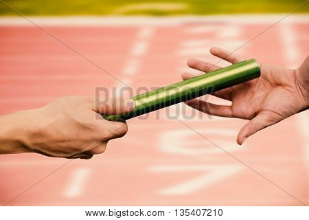 Man passing the baton to partner on track against close up of the track starting point