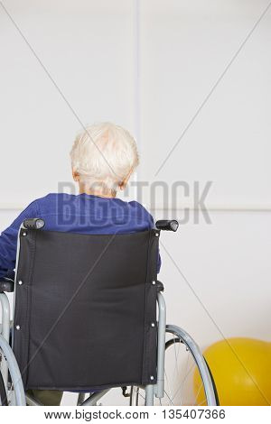 Senior woman sitting lonely in a wheelchair in a nursing home