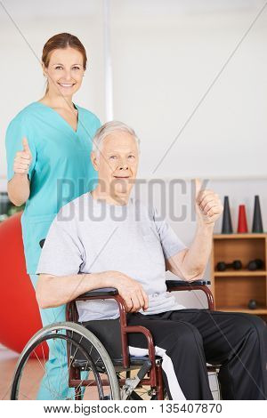 Old senior patient in wheelchair and geriatric nurse holding thumbs up