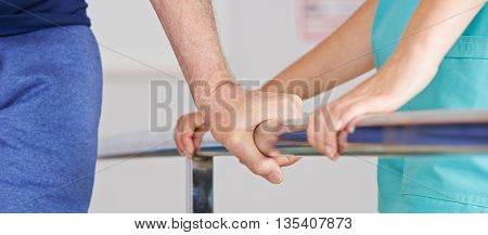 Hand of senior man on handle of treadmill in physiotherapy