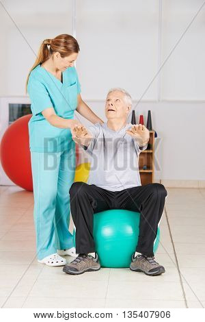 Senior man doing fitness exercise in physiotherapy on a gym ball