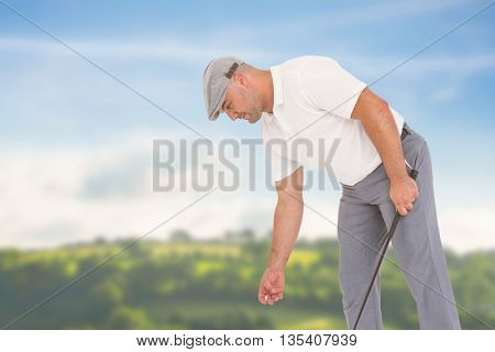 Golf player picking up golf ball against country scene