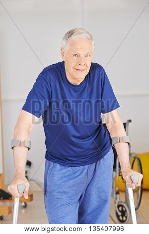 Old man with crutches learning to walk in rehab after an accident
