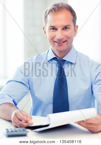 picture of handsome businessman with notebook and calculator