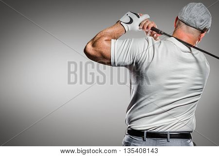 Portrait of golf player taking a shot against grey vignette