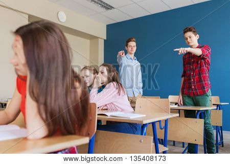 education, bullying, conflict, social relations and people concept - students teasing and judging girl classmate behind her back at school