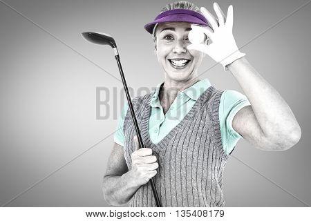 Pretty blonde playing golf against grey vignette