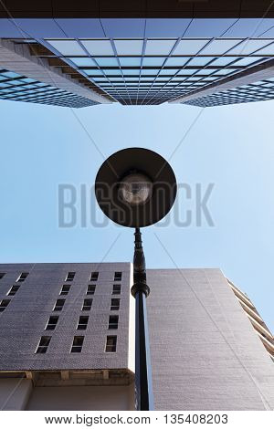 Lamp with lamppost and skyscraper under a blue sky