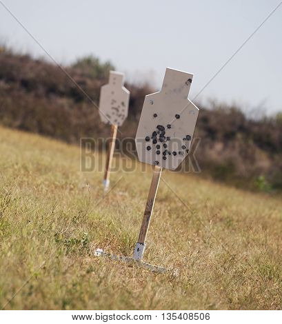 Pair of steel shilhouette targets being used for gun practice