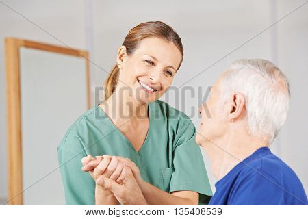 Smiling geriatric nurse holding hands with old senior man