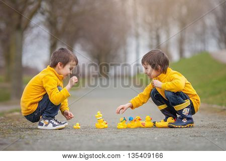 Two Adorable Children, Boy Brothers, Playing In Park With Rubber Ducks, Having Fun