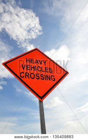 Road sign with a Heavy Vehicles Crossing against a partly cloudy sky background