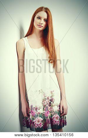 Tender portrait of beautiful redhead female wearing sleeveless flower print summer dress posing leaning against white wall. Tonned image