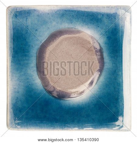 Blue handmade glazed ceramic tile with gray dot in middle isolated on white