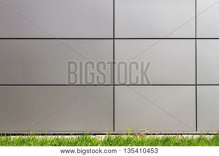 Modern dark tile wall and green grass