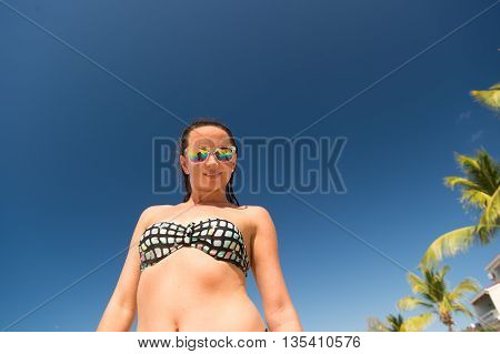 Young pretty woman in sun glasses with beautiful body in swimsuit standing sunny day outdoor on blue sky background