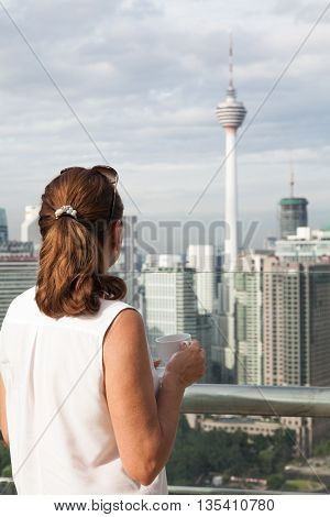 Woman with a cup of coffee on the top floor of a skyscraper admires the view of Kuala Lumpur.