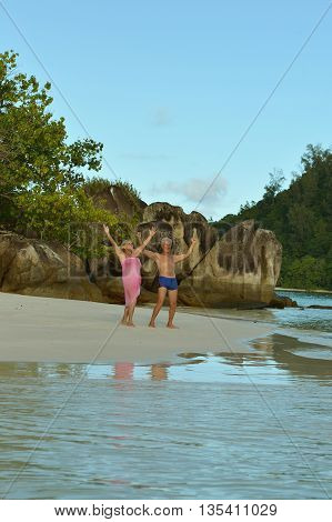 Happy elderly couple rest at tropical beach with hands up