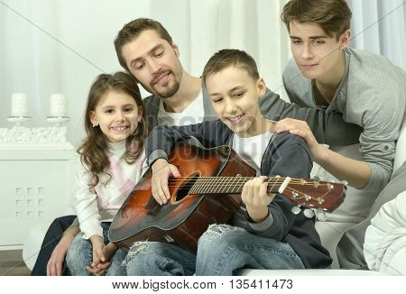young  boy  playing the guitar for his family