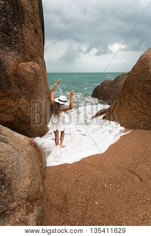 Lonely slender woman on a deserted beach on the background of large stones and a cloudy sky. She raised her arms and her legs flooded sea wave.