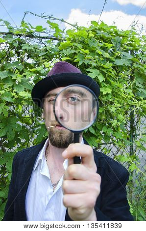 Eye in magnifying glass. The young bearded man looking through magnifying glass