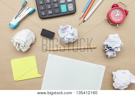 Business concept: post it,red clock,white blank paper,crumpled paper and color pencil,pencil,pen on brown paper background