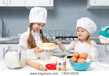 two smiling little girls-cooks cutting butter for dough on kitchen table