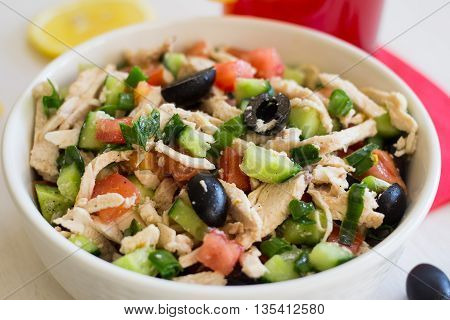 Greek salad with chicken in a white plate