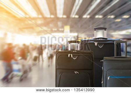 Closeup of group of luggage with the blurred of the airport terminal background.
